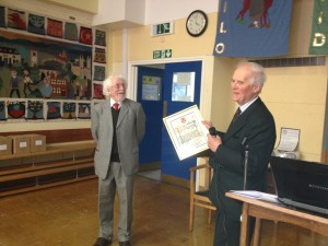 Ian Burge is presented with an illuminated scroll in recognition of his retirement as President of the Association.